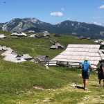 Two hikers in front reached huts on Velika Planina