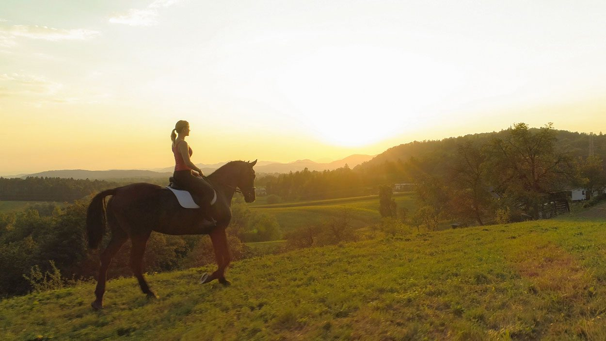 Woman riding horse with sunset