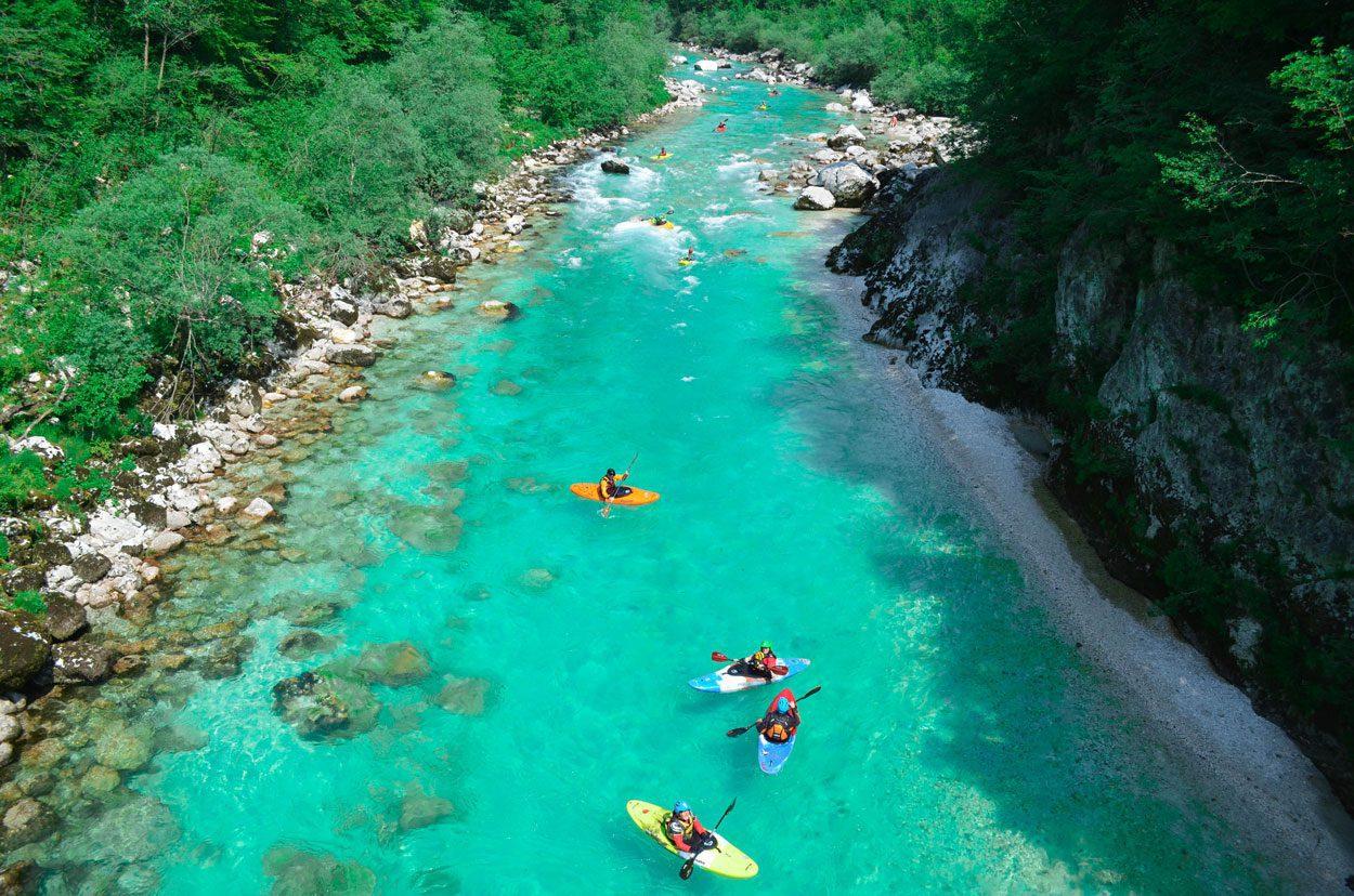Group kayaking down the Soča stream