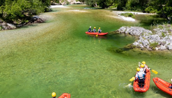 4 groups of people rafting in Bohinj