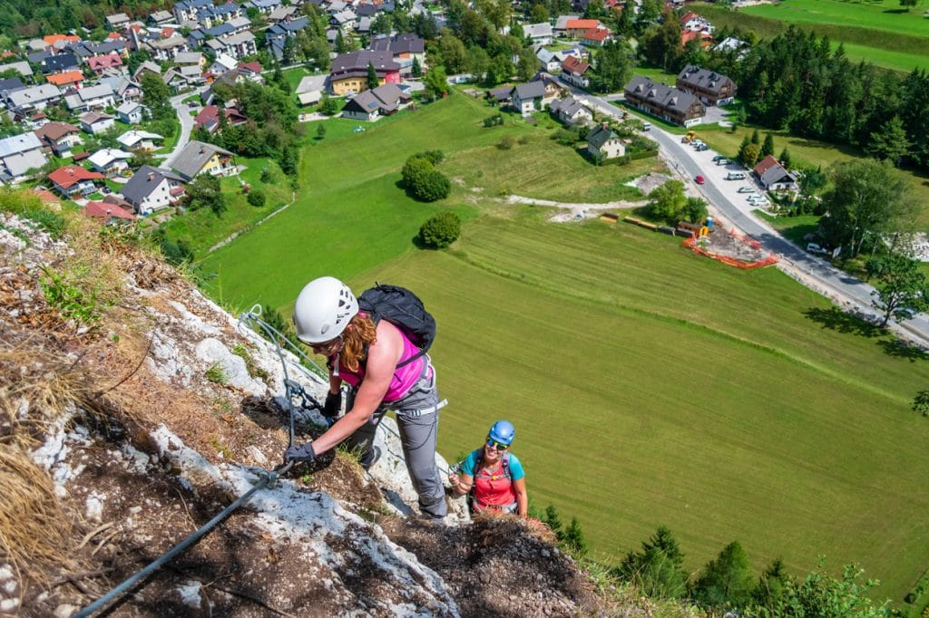 Woman climbing the rock wall on via ferrata experience